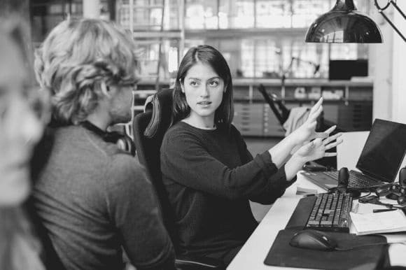 Software engineer sitting at her desk, explaining something to her colleague with expressive hands.