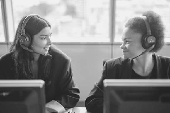A telemarketer and her colleague having a brief conversation between client calls.