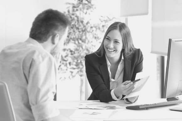 Benefits analyst talking with client in office