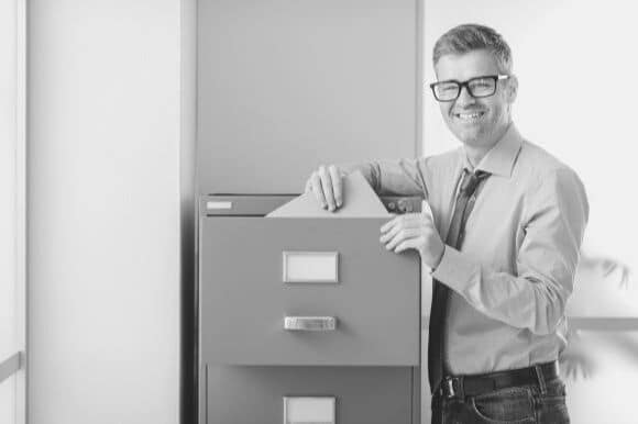 Medical records technician standing next to file cabinet in office