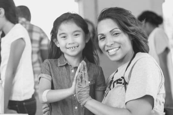 Public health nurse with child patient at community event