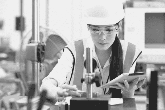 Quality engineer, wearing a hardhat, takes measurements of a part to determine whether it meets the company's standards.