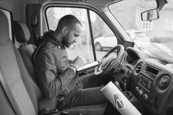 Delivery driver sitting in the front seat and entering orders into a device.
