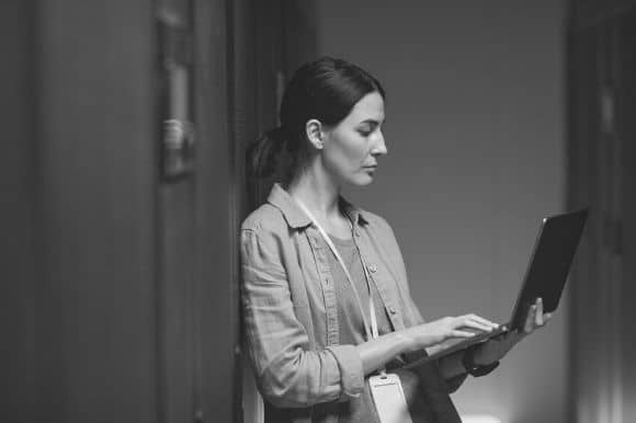 Data scientist, standing with her laptop, reviewing a project.