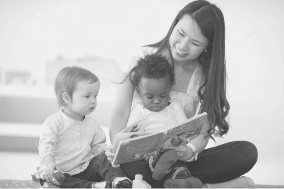 Babysitter sitting on the floor reading to two toddlers.