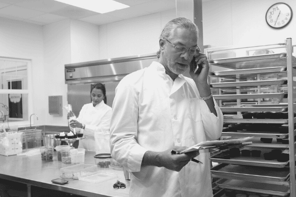 Executive chef on the telephone, restocking the kitchen, with a member of the kitchen staff working in the background.