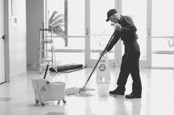 Janitor with mop and bucket, cleaning an office floor.