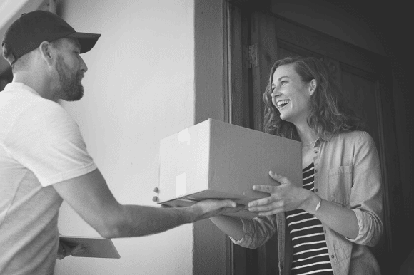 Mail carrier delivering a box to a happy customer.