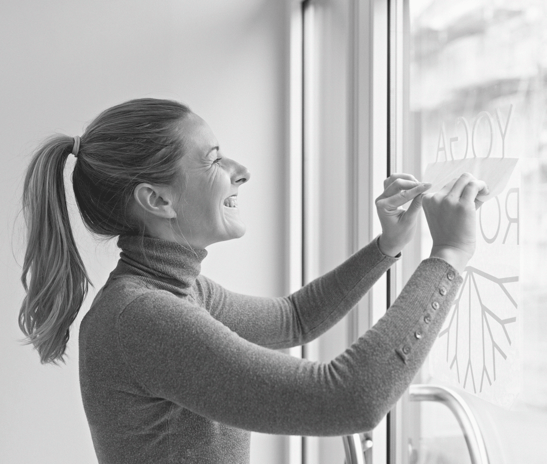 Woman applying decal to window